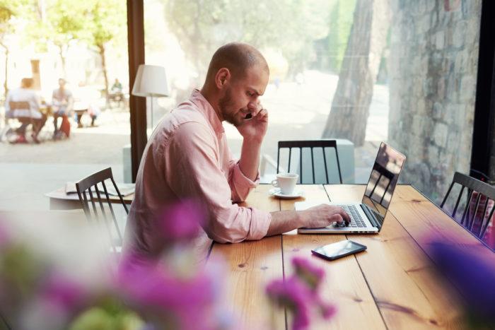 カフェでインターネットFAXの送受信をするフリーランス男性